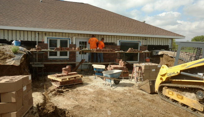 Two Basement RX masons working on laying the brick for the exterior of a house.